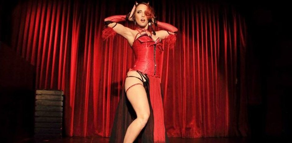 Live shot of burlesque dancer Kelly Ann Doll dressed in a devil costume on stage for Adelaide Fringe Festival