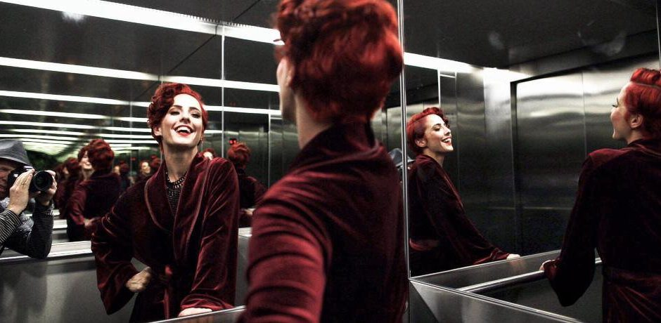 An image of Kelly Ann Doll posing in front of an elevator mirror giving the effect of many reflections, take by Johannes Reinhart