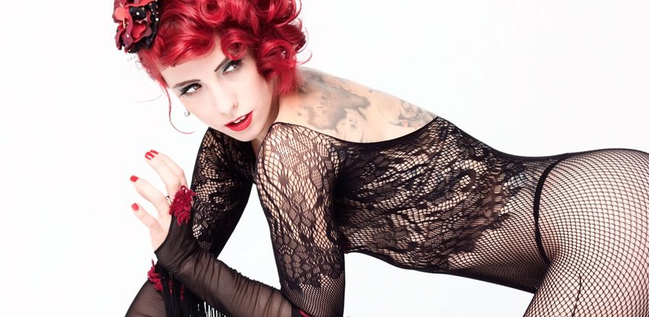 A studio image of burlesque dancer Kelly Ann Doll close up in a long sleeve lace body suit looking away from camera, shot by Peter Kelly