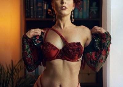 image of a Burlesque dancer with red hair wearing red lingerie near a window