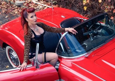 image of a woman with red hair wearing black lingerie getting into a red sports car