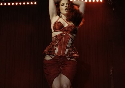 Image of a burlesque dancer on stage wearing a red costume at The Vanguard Sydney