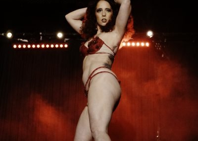 Image of a burlesque dancer on stage wearing red lingerie at The Vanguard Sydney