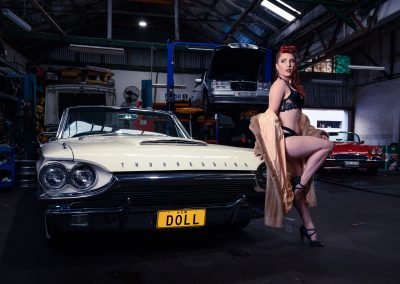 image of a woman with red hair wearing black lingerie standing next to a white Thunderbird Vintage Car